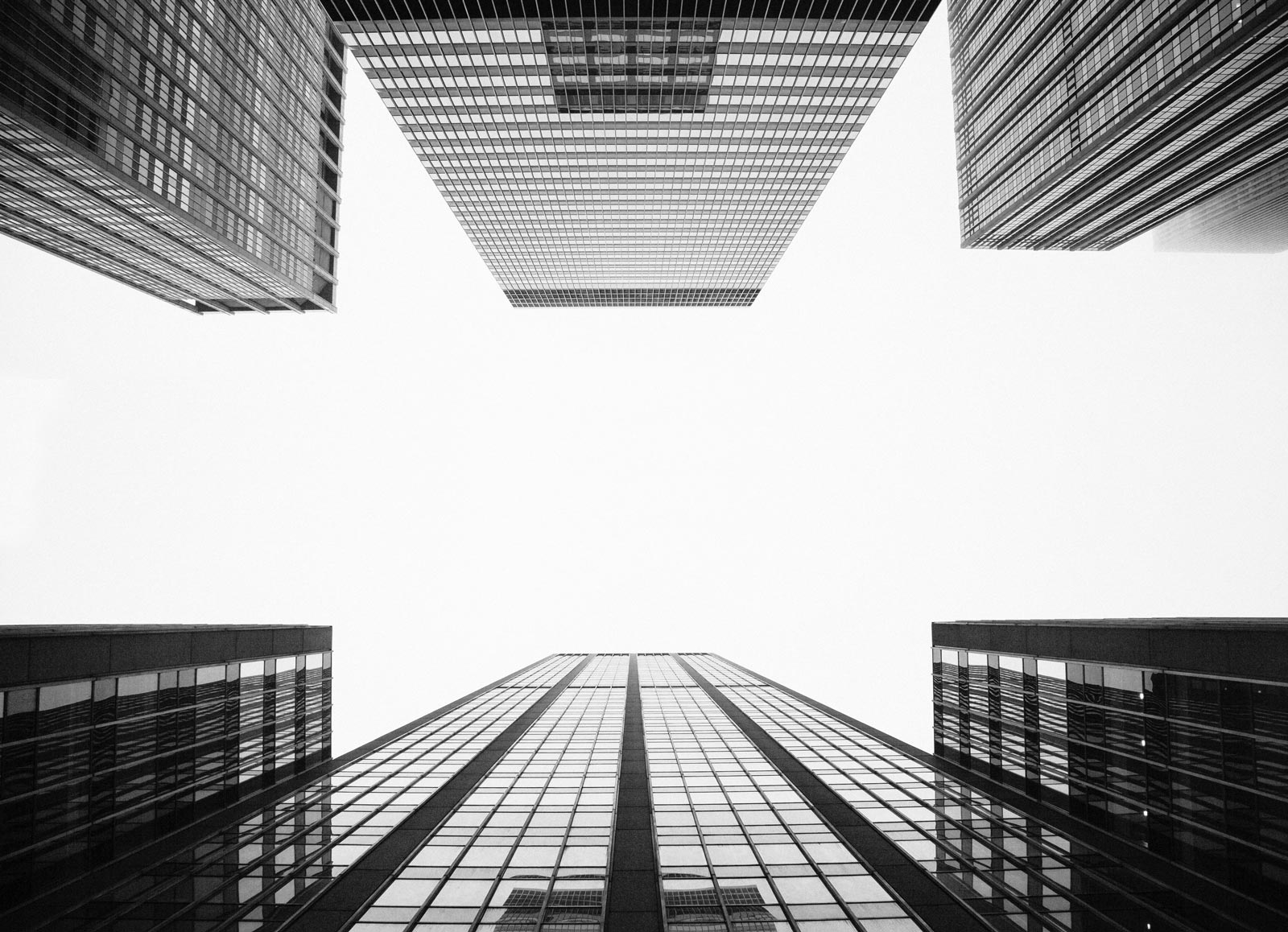 Black and white photo looking up at corporate buildings from the street